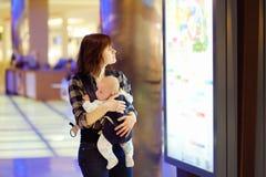 Kvinnan med henne behandla som ett barn i en shoppinggalleria Arkivfoton