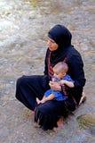Kvinnan med henne behandla som ett barn i floden av de Todra klyftorna i Marocko Arkivfoto