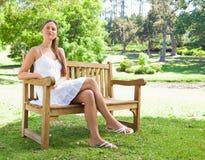 Kvinnan med henne ben korsade sammanträde på en bänk Royaltyfri Foto