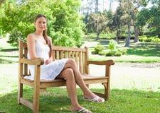 Kvinnan med henne ben korsade sammanträde på en parkerabänk Royaltyfri Bild