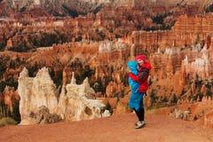 Kvinnan med hennes behandla som ett barn pojken fotvandrar i den Bryce kanjonen Arkivfoto
