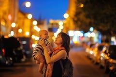 Kvinnan med hennes litet behandla som ett barn på nattstaden Arkivfoton