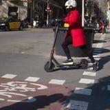 Kvinnan med hjälmen på elkraft skjuter sparkcykeln som pendlar i centrala Barcelona royaltyfria bilder