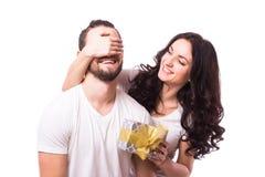 Kvinnan med hållande pojkvänner för det stora toothy leendet synar ge honom en gåva för valentins dag Royaltyfri Bild