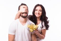 Kvinnan med hållande pojkvänner för det stora toothy leendet synar ge honom en gåva för valentins dag Royaltyfri Fotografi
