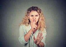 Kvinnan med hyssjar är den tysta gesten på grå bakgrund Royaltyfri Foto