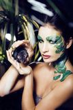 Kvinnan med idérikt smink som orm och tjaller i hennes händer som är hal Arkivbilder
