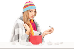Kvinnan med influensainnehav en termometer, boxas med pappers- tisssues på Arkivbilder