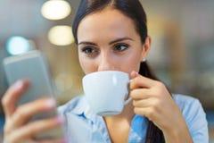 Kvinnan med kaffe och ilar telefonen fotografering för bildbyråer