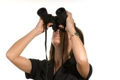 Kvinnan med kikare ser upp Arkivfoto