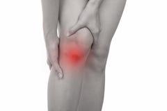 Kvinnan med knäkänsla smärtar på vit bakgrund Royaltyfri Fotografi