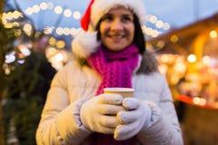 Kvinnan med koppen av den varma drinken på jul marknadsför Arkivfoto