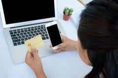 Kvinnan med kreditkorten och ilar telefonen Arkivfoton