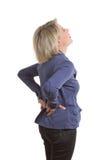 Kvinnan med lågt tillbaka smärtar Arkivfoto