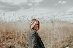 Kvinnan med lång iklädd ull för blont hår täcker att se kameran över hennes skuldra royaltyfri foto