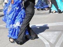 Kvinnan med långa blått klär dans med en utomhus- man Arkivbild