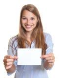 Kvinnan med långt blont hår har ett tomt gåvakort för jul i hennes händer royaltyfria foton