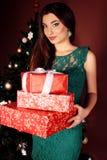 Kvinnan med långt mörkt hår snör åt in den gröna klänningen rymma julklappar fotografering för bildbyråer