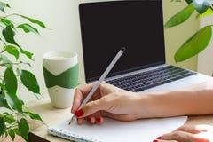 Kvinnan med ljus manikyr skriver med blyerts i dagbok Bredvid till tabellen är bärbara datorn, koppen av vatten med citron- och g Royaltyfri Bild