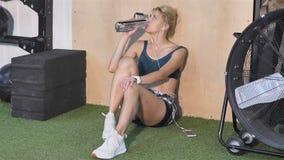 Kvinnan med lockigt hår sitter på golvet i idrottshallen på bakgrunden av delningen Hon bär den mörka sportswearen med stock video