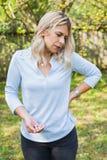 Kvinnan med lumbalt smärtar arkivfoto