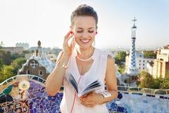 Kvinnan med lyssnande audioguide för turist- handbok parkerar in Guell royaltyfri bild