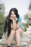 Kvinnan med mycket långt sammanträde för svart hår vaggar på Arkivfoton