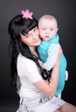 Kvinnan med nyfött behandla som ett barn royaltyfri foto