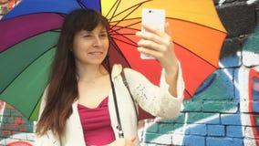 Kvinnan med paraplyet använder en telefon bredvid väggen med grafitti stock video