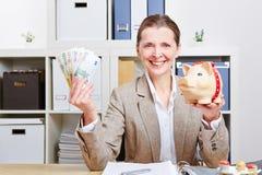 Kvinnan med piggy packar ihop och euroen Arkivbilder