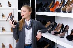 Kvinnan med pumpen i hand väljer skor royaltyfria bilder
