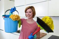 Kvinnan med rött hår i rubber tvagninghandskar som rymmer lokalvårdhinken, moppar och sopar Arkivbild