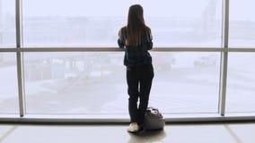 Kvinnan med ryggsäcken går till flygplatsfönstret Lycklig lyckad europeisk passagerareflicka med smartphonen i terminal 4K Fotografering för Bildbyråer