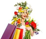 Kvinnan med shopping hänger lös den hållande blomman. Arkivbild