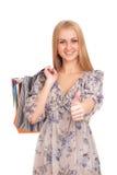 Kvinnan med shopping hänger lös upp göra en gest tum Royaltyfri Bild