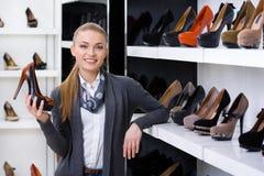 Kvinnan med skon i hand väljer höjdpunkten heeled skor royaltyfri fotografi