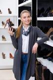 Kvinnan med skon i hand väljer pumpar fotografering för bildbyråer
