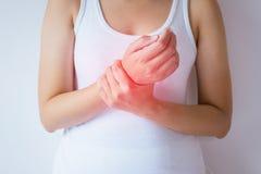Kvinnan med smärtar i handleden, den kvinnliga handen som trycker på hennes smärtsamma manschett royaltyfria bilder