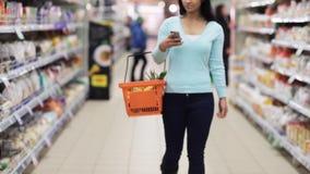 Kvinnan med smartphone- och matkorgen på shoppar arkivfilmer