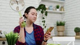 Kvinnan med smartphonen i hand äter selleri på kök arkivfilmer