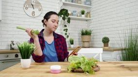 Kvinnan med smartphonen i hand äter selleri på kök stock video