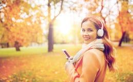 Kvinnan med smartphonen och hörlurar i höst parkerar Royaltyfri Fotografi