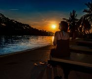 Kvinnan med solglasögon ser in i solnedgången arkivfoton