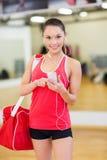 Kvinnan med sportar hänger löst, smartphonen och hörlurar Arkivbild