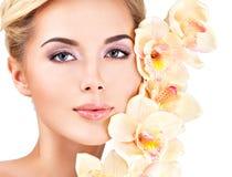 Kvinnan med sund hud och blommor vänder mot nästan arkivbild