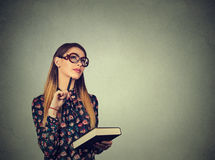 Kvinnan med tänkande drömma för bok har många idéer som ser upp royaltyfria bilder