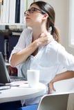 Kvinnan med tillbaka smärtar på arbete Arkivfoto