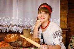 Kvinnan med träkavlen bakar bröd Royaltyfri Bild