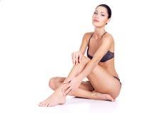 Kvinnan med vård- förkroppsligar, och long slankt lägger benen på ryggen arkivbild