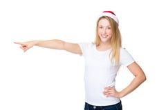 Kvinnan med xmas-hatten och fingret pekar åt sidan royaltyfri foto